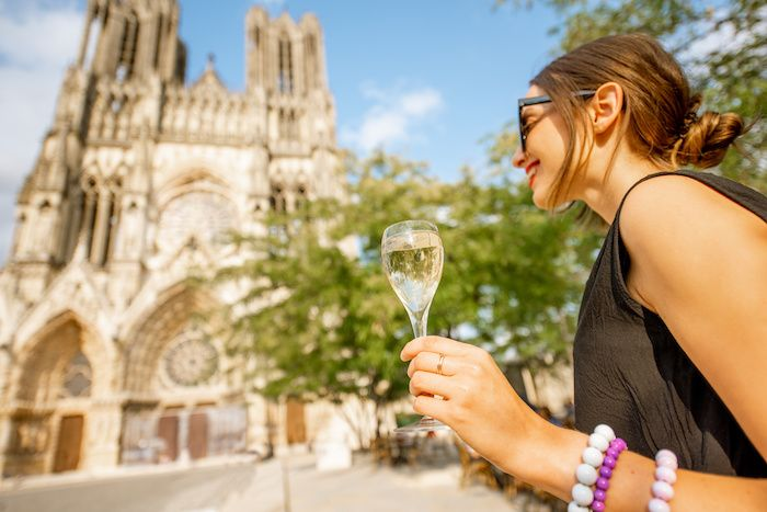 Young woman enjoying champagne standing in front of the cathedral in Reims city, capital of Champagne wine region, France
