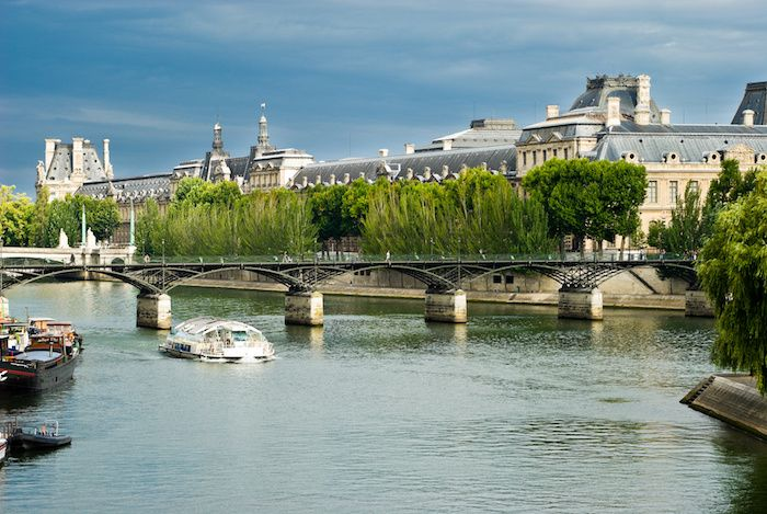 View of the famous museum Louvre from the Seine river. Paris, France.